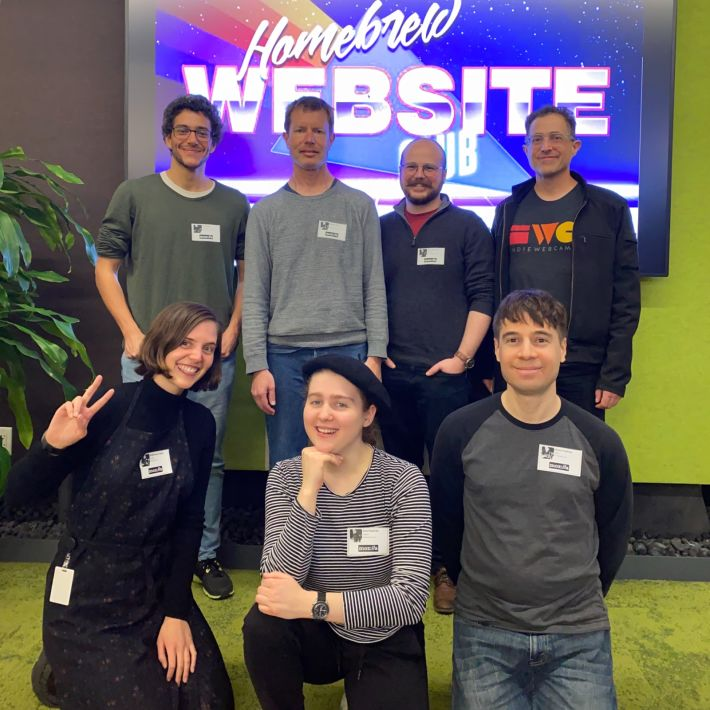Participants of HWC San Francisco pose in two rows in front of a large screen displaying an 80s style Homebrew Website Club logo in the commons room at Mozilla San Francisco.